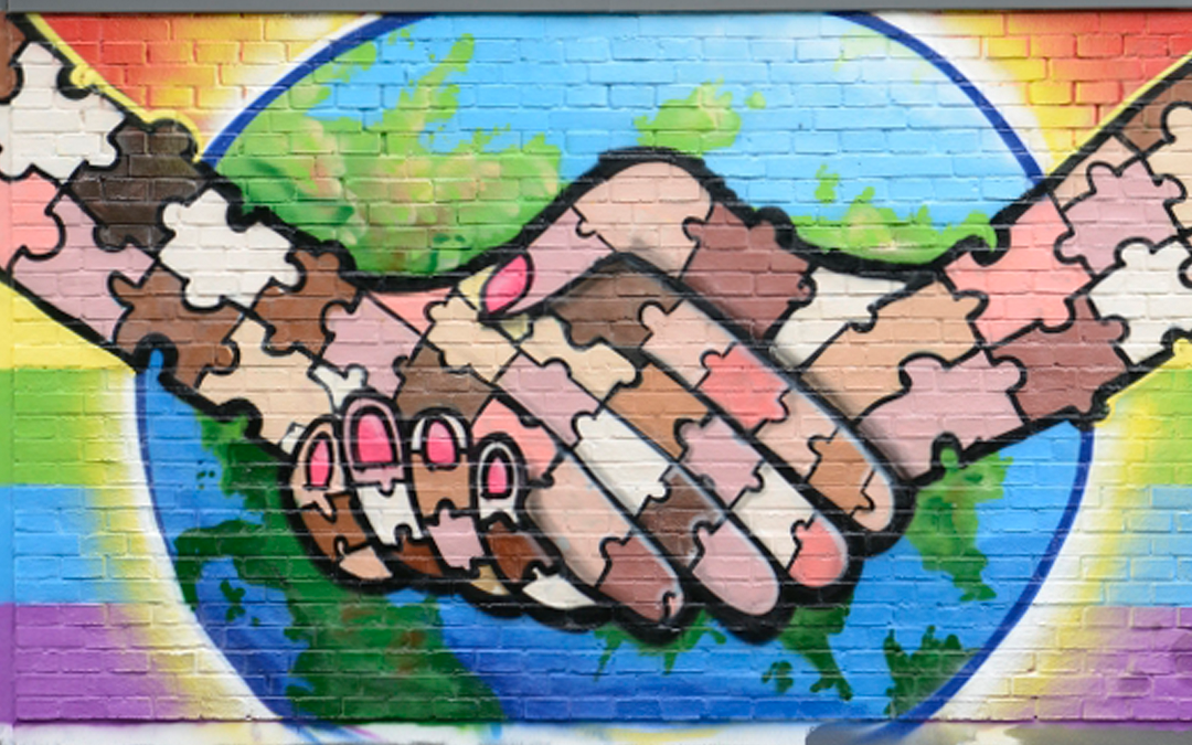 Hand in Hand: gemeinsam statt gegeneinander! Schüler*innen der Gymnasien für Erwachsene sprayen Graffito für Respekt und Solidarität